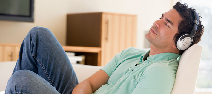 Man on couch with headphones listening