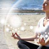 Lady on beach meditating with a bubble around her